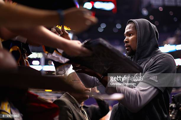 Kevin Durant of the Golden State Warriors signs autographs for fans before the NBA game against the Phoenix Suns at Talking Stick Resort Arena on...