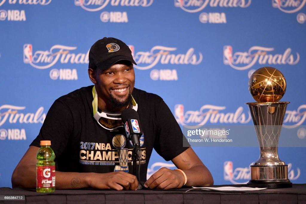 Kevin Durant #35 of the Golden State Warriors speaks to members of the media with the Bill Russell NBA Finals Most Valuable Player Award after defeating the Cleveland Cavaliers 129-120 in Game 5 to win the 2017 NBA Finals at ORACLE Arena on June 12, 2017 in Oakland, California.