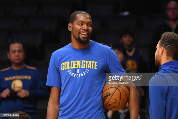 Kevin Durant of the Golden State Warriors speaks with Stephen Curry of the Golden State Warriors before the game against the Los Angeles Lakers on...