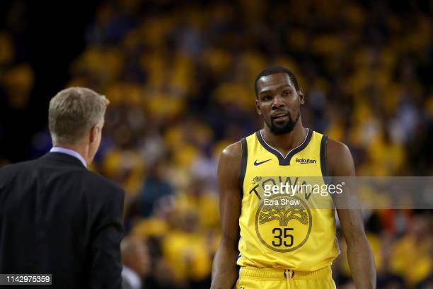 Kevin Durant of the Golden State Warriors talks to head coach Steve Kerr during Game Two of the first round of the 2019 NBA Western Conference...