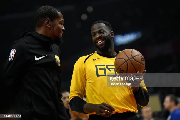 Kevin Durant of the Golden State Warriors talks to his teamate Draymond Green during warm up before the game against the Los Angeles Clippers on...