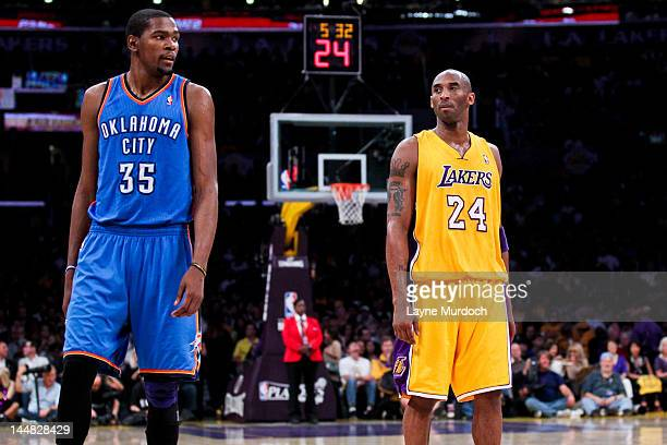 Kevin Durant of the Oklahoma City Thunder and Kobe Bryant of the Los Angeles Lakers wait to resume action in Game Four of the Western Conference...