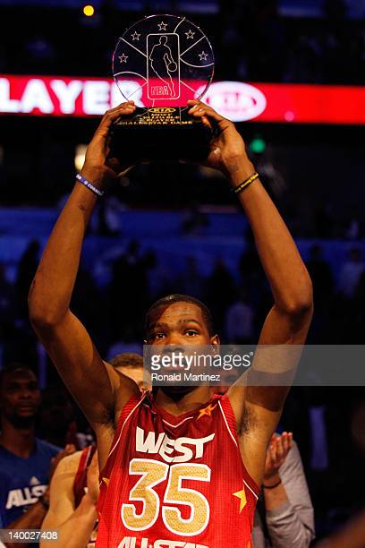 Kevin Durant of the Oklahoma City Thunder and the Western Conference holds up the MVP trophy after the West won 152-149 against Eastern Conference...