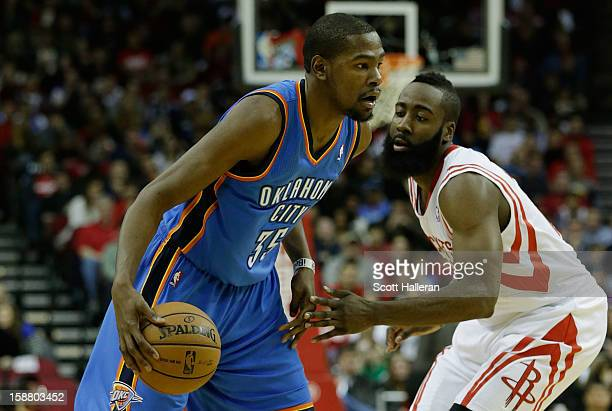 Kevin Durant of the Oklahoma City Thunder drives past James Harden of the Houston Rockets at the Toyota Center on December 29 2012 in Houston Texas...