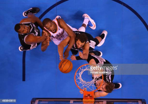 Kevin Durant of the Oklahoma City Thunder drives to the basket against Boris Diaw Marco Belinelli and Tiago Splitter of the San Antonio Spurs in the...