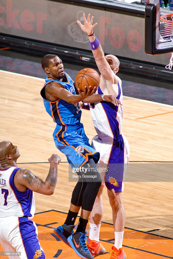 Kevin Durant #35 of the Oklahoma City Thunder drives to the basket against Marcin Gortat #4 of the Phoenix Suns on January 14, 2013 at U.S. Airways Center in Phoenix, Arizona.
