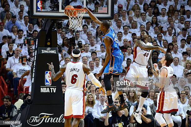 Kevin Durant of the Oklahoma City Thunder dunks in the first half against LeBron James and Udonis Haslem of the Miami Heat in Game Five of the 2012...