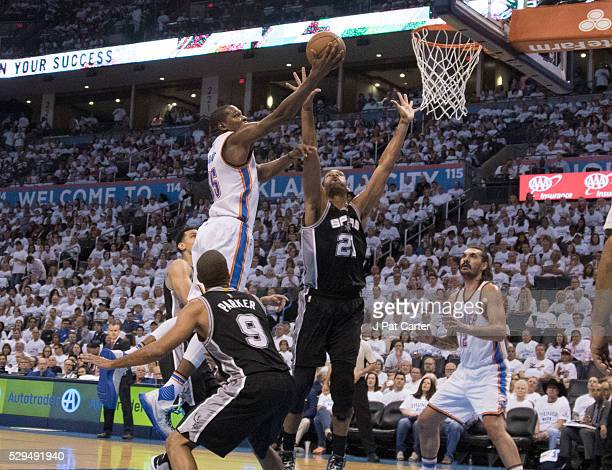 Kevin Durant of the Oklahoma City Thunder flies past Tony Parker of the San Antonio Spurs and Tim Duncan of the San Antonio Spurs for two points...
