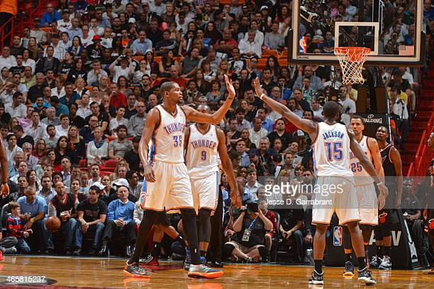 Kevin Durant of the Oklahoma City Thunder gives a high five to teammate Reggie Jackson against the Miami Heat at the American Airlines Arena in Miami...