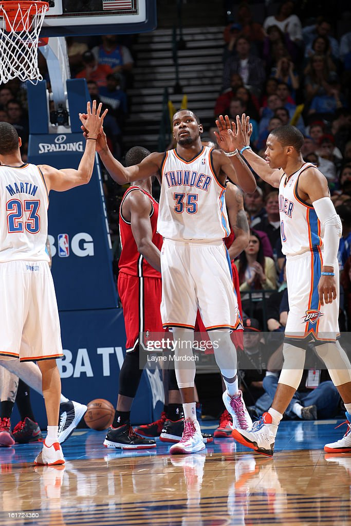 Kevin Durant #35 of the Oklahoma City Thunder gives high fives to his teammates during an NBA game on February 14, 2013 at the Chesapeake Energy Arena in Oklahoma City, Oklahoma.