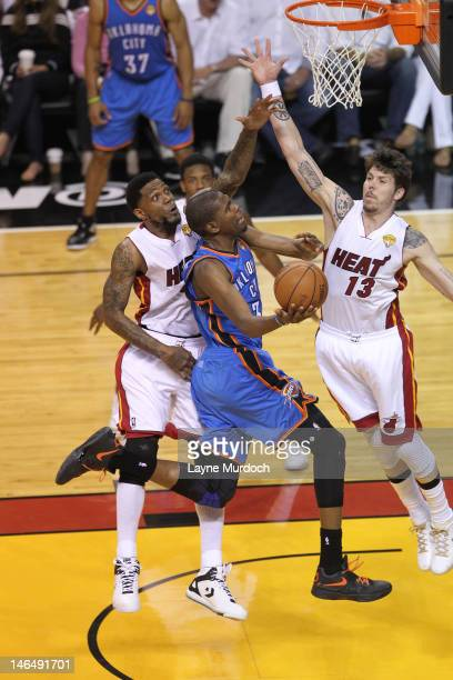 Kevin Durant of the Oklahoma City Thunder goes to the basket against Udonis Haslem and Mike Miller of the Miami Heat during Game Three of the 2012...
