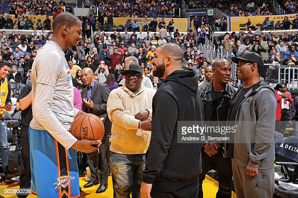 Kevin Durant of the Oklahoma City Thunder greets rapper Drake and actors Cedric the Entertainer and Denzel Washington before the game against the Los...