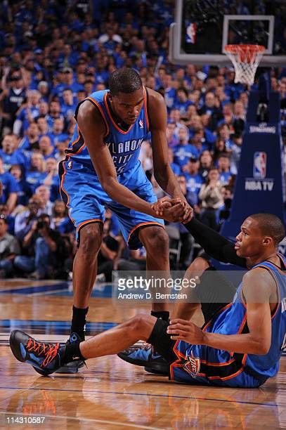 Kevin Durant of the Oklahoma City Thunder helps up Russell Westbrook during Game One of the Western Conference Finals against the Dallas Mavericks in...