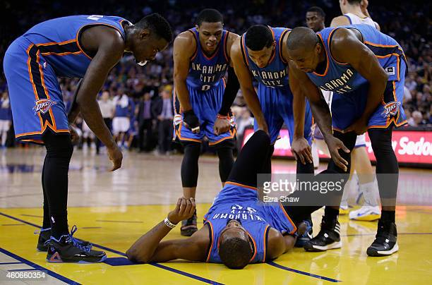 Kevin Durant of the Oklahoma City Thunder holds his ankle as his teammates check to see if he is okay after he twisted his ankle towards the end of...