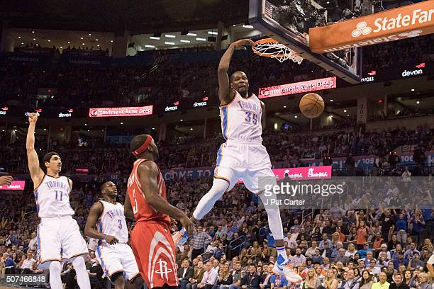 Kevin Durant of the Oklahoma City Thunder runs past Ty Lawson of the Houston Rockets to dunk two points during the third quarter of a NBA game at the...