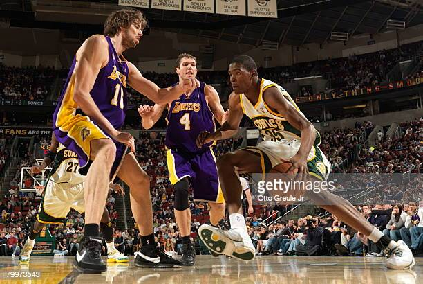 Kevin Durant of the Seattle SuperSonics drives against Pau Gasol and Luke Walton of the Los Angeles Lakers at Key Arena February 24 2008 in Seattle...