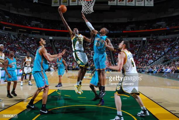 Kevin Durant of the Seattle SuperSonics goes to the basket between the defense of Tyson Chandler and David West of the New Orleans Hornets on...