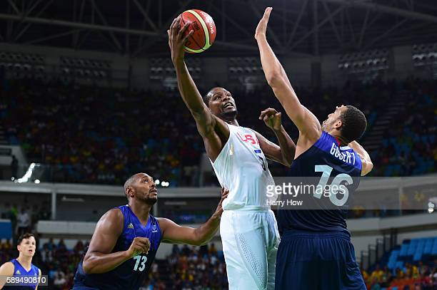 Kevin Durant of United States shoots against Rudy Gobert of France while Boris Diaw of France looks on during a Men's Preliminary Round Group A game...