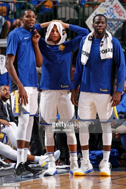 Kevin Durant Stephen Curry and Draymond Green of the Golden State Warriors look on from the bench after the dunk by Jordan Bell during the game...