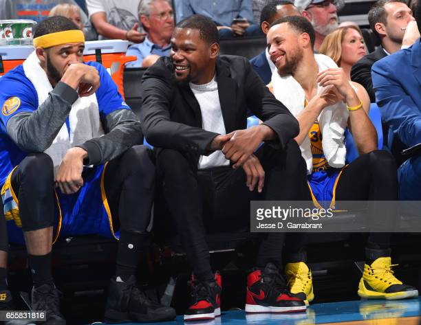 Kevin Durant Stephen Curry and JaVale McGee of the Golden State Warriors all look on against the Oklahoma City Thunder during the game on March 20...