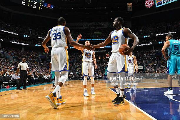 Kevin Durant Stephon Curry and Draymond Green of the Golden State Warriors give each other fives against the Charlotte Hornets at Spectrum Center on...