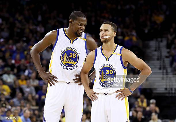 Kevin Durant talks to Stephen Curry of the Golden State Warriors during their game against the Los Angeles Clippers during their preseason game at...