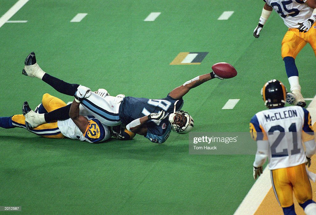 Kevin Dyson #87 of the Tennessee Titans reaches for the end zone with the ball as Mike Jones #52 of the St. Louis Rams tackles him on the last play of the game during the Super Bowl XXXIV Game at the Georgia Dome on January 30, 2000 in Atlanta, Georgia. The Rams defeated the Titans 23-16.