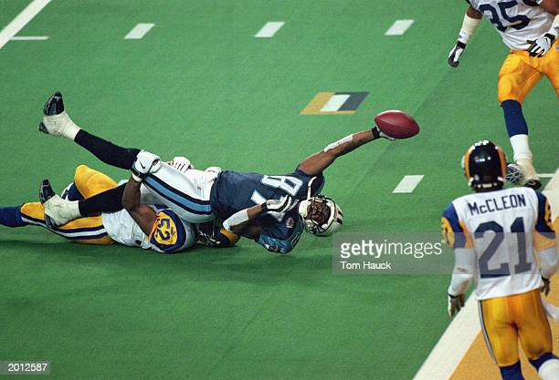Kevin Dyson of the Tennessee Titans reaches for the end zone with the ball as Mike Jones of the St Louis Rams tackles him on the last play of the...
