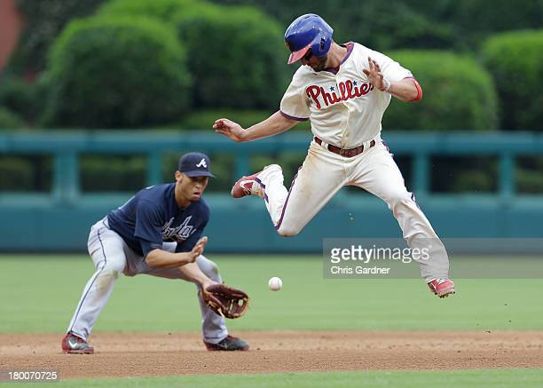 Kevin Fandsen of the Philadelphia Phillies leaps to get out of the way of a ball hit by Freddy Galvis as Andrelton Simmons of the Atlanta Braves...