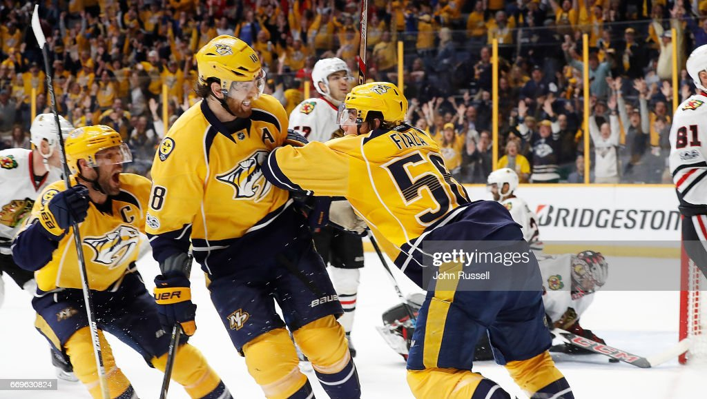 Kevin Fiala #56 celebrates his overtime game winning goal with James Neal #18 and Mike Fisher #12 of the Nashville Predators against the Chicago Blackhawks in Game Three of the Western Conference First Round during the 2017 NHL Stanley Cup Playoffs at Bridgestone Arena on April 17, 2017 in Nashville, Tennessee.