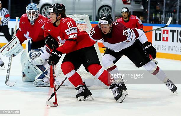 Kevin Fiala of Switzerland and Andris Dzernis of Latvia battle for the puck during the IIHF World Championship group A match between Switzerland and...