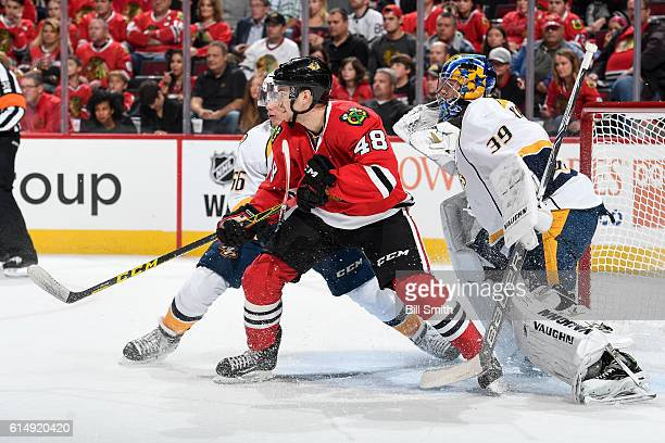 Kevin Fiala of the Nashville Predators and Vinnie Hinostroza of the Chicago Blackhawks wait in position in front of goalie Marek Mazanec in the first...