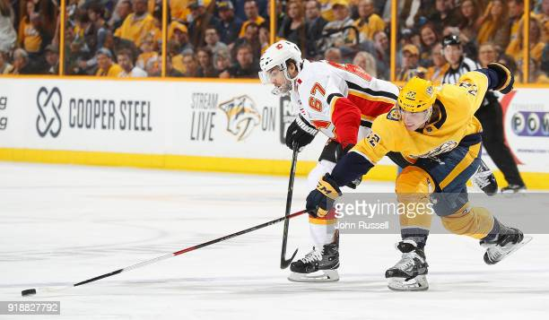 Kevin Fiala of the Nashville Predators battles for the puck against Michael Frolik of the Calgary Flames during an NHL game at Bridgestone Arena on...