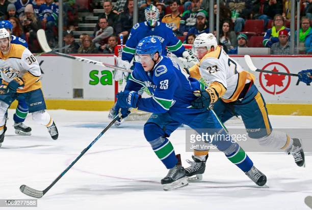 Kevin Fiala of the Nashville Predators checks Bo Horvat of the Vancouver Canucks during their NHL game at Rogers Arena December 6, 2018 in Vancouver,...