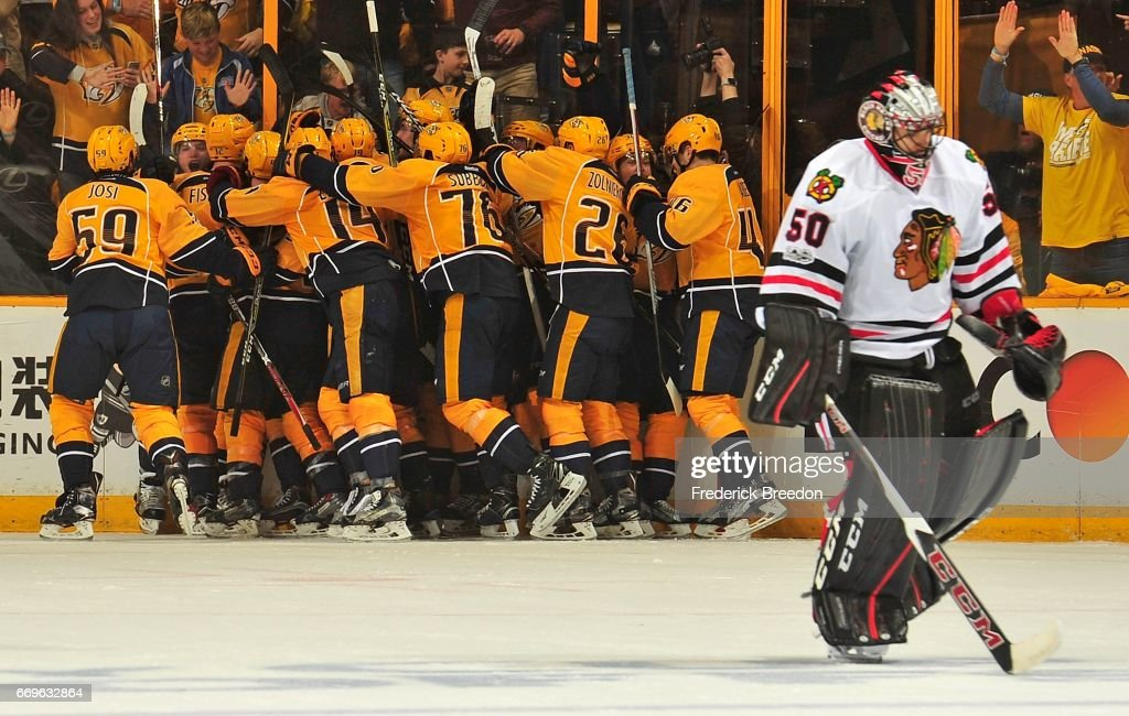 Kevin Fiala #56 of the Nashville Predators is swarmed by teammates after scoring the game winning overtime goal against goalie Corey Crawford #50 of the Chicago Blackhawks in Game Three of the Western Conference First Round during the 2017 NHL Stanley Cup Playoffs at Bridgestone Arena on April 17, 2017 in Nashville, Tennessee.