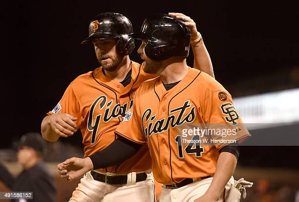 Kevin Frandsen and Jackson Williams of the San Francisco Giants celebrates after they both scored against the Colorado Rockies in the bottom of the...