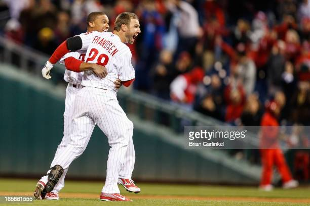 Kevin Frandsen of the Philadelphia Phillies is congratulated by a teammate after hitting a three RBI double to win the game in the bottom of the...