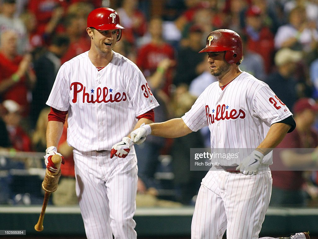 Kevin Frandsen #28 of the Philadelphia Phillies is congratulated by teammate Kyle Kendrick #38 after hitting a home run in the second inning against the Atlanta Braves during a MLB baseball game on September 21, 2012 at Citizens Bank Park in Philadelphia, Pennsylvania. The Phillies defeated the Braves 6-2.