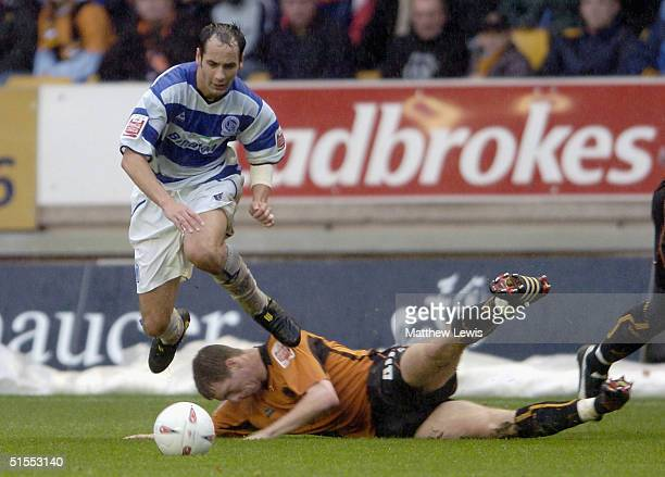 Kevin Gallan of QPR beats the tackle from Mikkel Bischoff of Wolves during the CocaCola Championship match between Wolverhampton Wanderers and Queens...