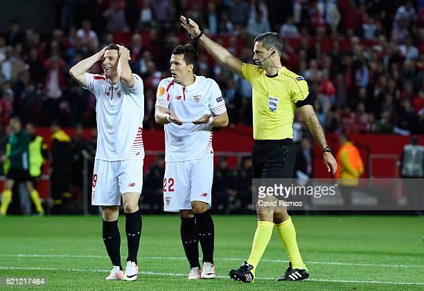 Kevin Gameiro and Yevhen Konoplyanka of Sevilla react with referee Damir Skomina during the UEFA Europa League quarter final second leg match between...
