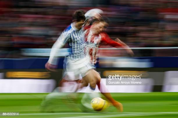 Kevin Gameiro of Atletico de Madrid competes for the ball with Mikel Oyarzabal of Real Sociedad de Futbol during the La Liga match between Club...