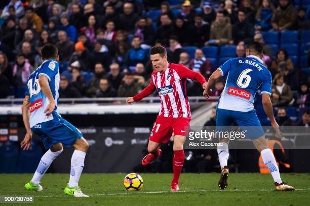 Kevin Gameiro of Atletico de Madrid plays the ball between Javi Lopez and Oscar Duarte of RCD Espanyol during the La Liga match between Espanyol and...