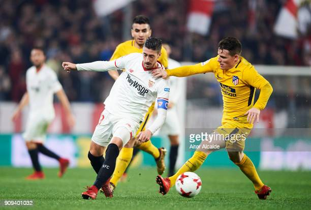 Kevin Gameiro of Atletico Madrid duels for the ball with Sergio Escudero of Sevilla FC during the Copa del Rey Quarter Final second Leg match between...
