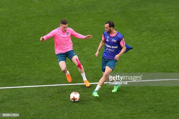 Kevin Gameiro of Atletico Madrid looks on as Diego Godin of Atletico Madrid controls the ball during a Club Atletico de Madrid training session ahead...