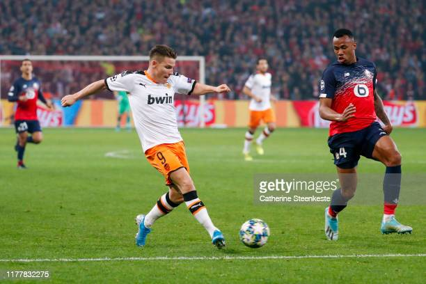 Kevin Gameiro of Valencia CF shoots the ball against Gabriel Dos Santos of Losc during the UEFA Champions League group H match between Lille OSC and...