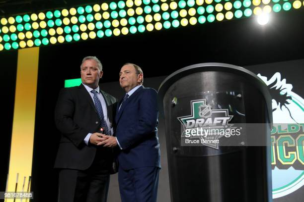 Kevin Garinger president of the Humboldt Broncos and NHL commissioner Gary Bettman shake hands onstage after accepting the EJ McGuire Award of...