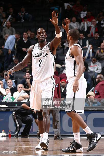 Kevin Garnett of the Brooklyn Nets highfives teammate Alan Anderson during a game against the Philadelphia 76ers at Barclays Center on December 16...