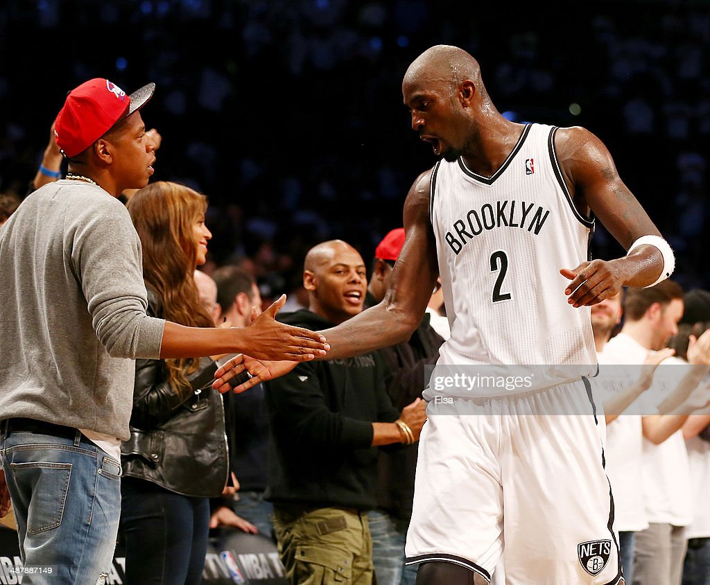 Kevin Garnett #2 of the Brooklyn Nets is congratulated by Jay-Z after Garnett was pulled from the game in the fourth quarter against the Toronto Raptors in Game Six of the Eastern Conference Quarterfinals during the 2014 NBA Playoffs at the Barclays Center on May 2, 2014 in the Brooklyn borough of New York City.