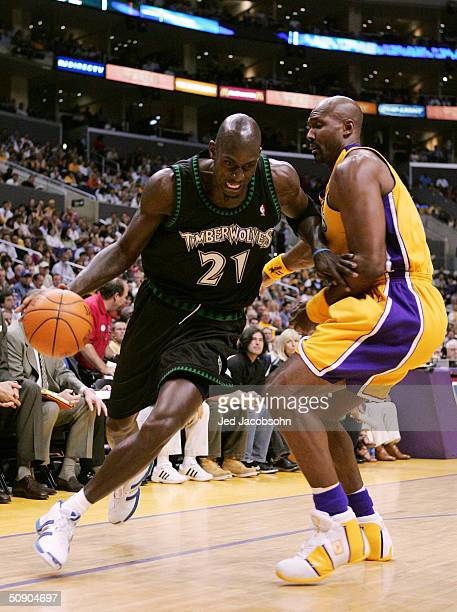 Kevin Garnett of the Minnesota Timberwolves drives past Karl Malone of the Los Angeles Lakers in the first half of Game 4 of the Western Conference...