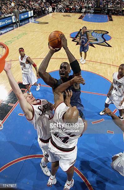Kevin Garnett of the Minnesota Timberwolves goes up for the shot against Keith Van Horn and Derrick Coleman of the Philadelphia 76ers during the NBA...